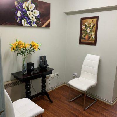 Espacio de espera para pacientes y/o acompañantes. Se aprecian una mesa y 2 sillas.